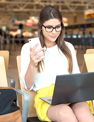 Woman working at airport on mobile device
